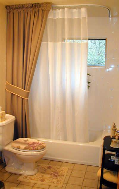 L-shaped ceiling mounted shower rod featuring white shower curtain with mesh and decorative curtain